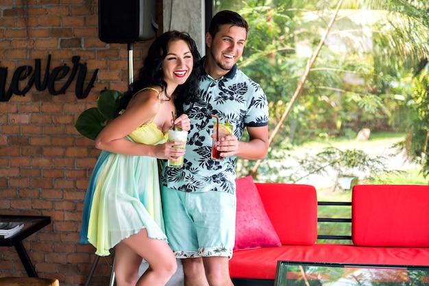 Positives innenporträt des glücklichen paares, das zeit im stilvollen tropischen restaurant verbringt, trendige outfits, beziehungspaarziele.