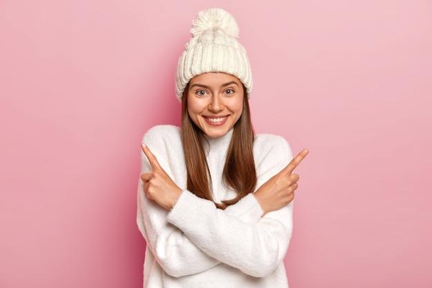Positives junges mädchen mit glattem haar, verschränkten armen und spitzen auf beiden seiten, trägt modischen weißen hut und pullover, wählt zwischen zwei gegenständen