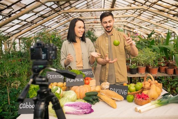Positives junges multiethnisches paar, das videobewertung über bio-lebensmittel auf gewächshausfarm schießt
