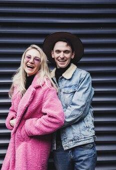 Positives junges paar, das in den straßen der stadt lacht