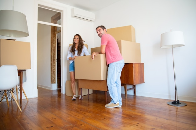Positives junges paar, das über ihre neue wohnung schaut, während sie steht und sich auf pappkartons und möbel drinnen stützt