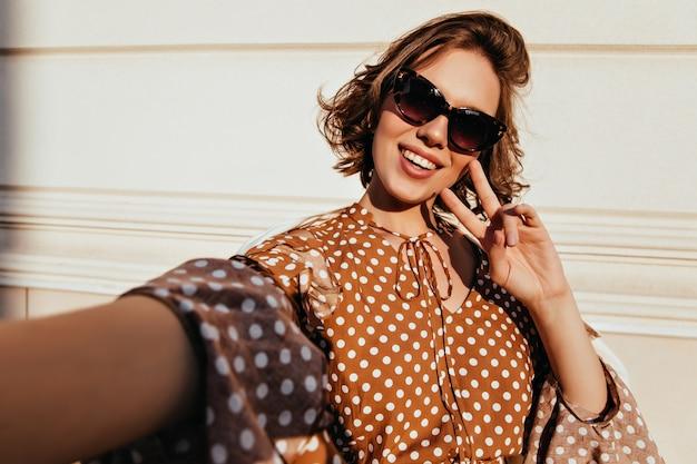 Positives junges weibliches modell mit tätowierungen, die auf städtischer straße herumalbern. prächtiges lockiges mädchen, das selfie macht.