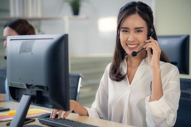 Positives lächeln der geschäftsfrau mit dem callcenter-betreiber des headsets helfen problemtechnologie-kundenunterstützung