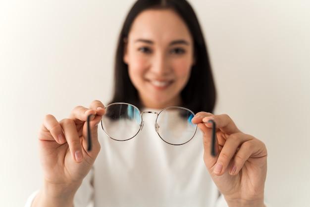 Positives lächelndes asiatisches mädchen, das eine brille hält und die sauberkeit überprüft, während es auf einem weißen wandhintergrund posiert. fokus auf die hände mit brille