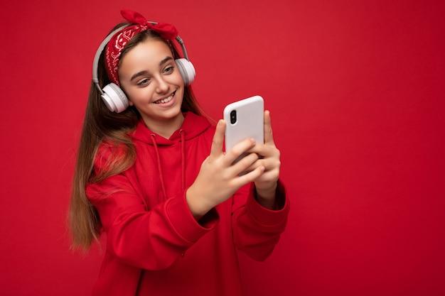 Positives lächelndes attraktives brünettes mädchen, das roten hoodie auf rotem hintergrund hält und isoliert trägt