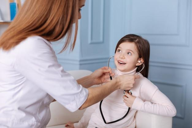 Positives lächelndes mädchen, das stethoskop benutzt, während professioneller docotr sie unterstützt