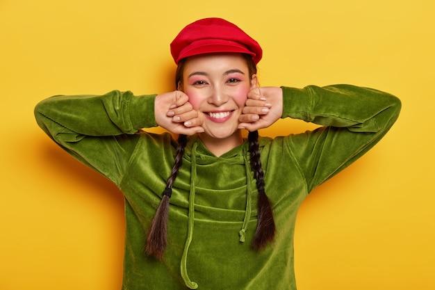 Positives mädchen berührt wangen, hält hände zur seite, lächelt angenehm, trägt rote baskenmütze und grünes samt-sweatshirt