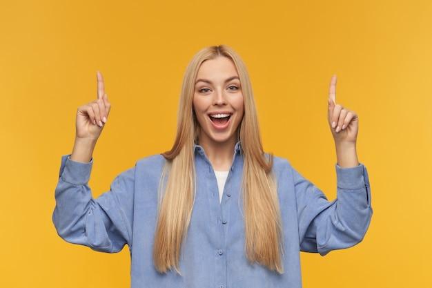 Positives mädchen, glücklich aussehende frau mit blonden langen haaren. blaues hemd tragen. menschen- und emotionskonzept. beobachten sie die kamera und zeigen sie mit den fingern nach oben auf den kopierbereich, isoliert über dem orangefarbenen hintergrund