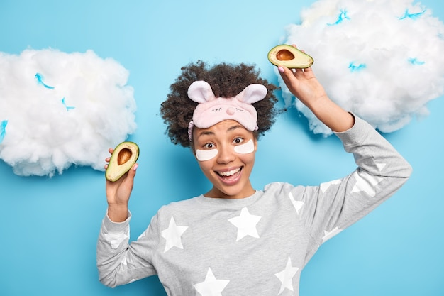 Positives mädchen hebt hände mit hälften der avocado genießt glücklichen tag gekleidet in pyjama-augenbinde auf stirnlächeln unterzieht sich allgemein schönheitsbehandlungen, die kollagenflecken unter den augen anwenden