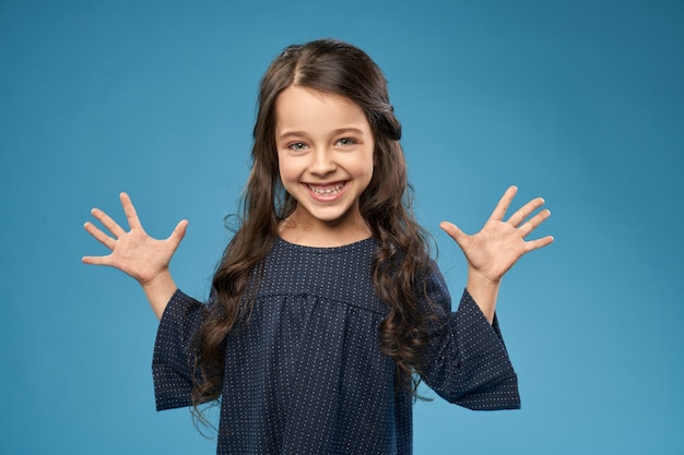 Positives mädchen im grauen kleid, das finger, hände zeigt.