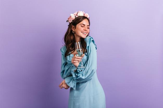 Positives mädchen in hochstimmung lacht, während party auf lila wand genießt. modell im blauen outfit mit glas champagner.