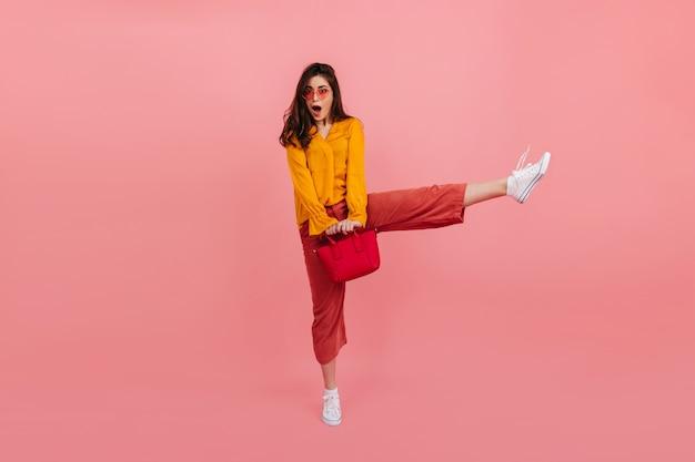 Positives mädchen in modischen hellen kleidern springt hoch auf rosa wand. porträt der überraschten brünetten in voller länge mit roter tasche.