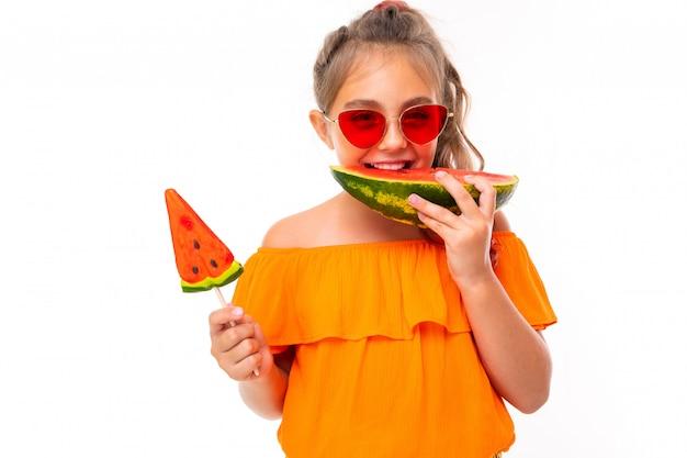 Positives mädchen isst eine wassermelone und hält einen lutscher in den händen, schaut mit roter sonnenbrille in die kamera
