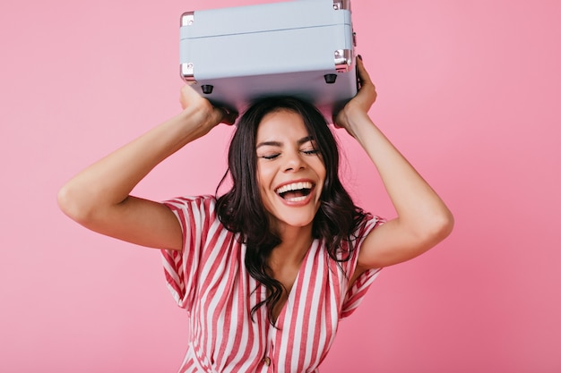 Positives mädchen lacht mit geschlossenen augen mit koffer auf dem kopf. porträt der brünetten in guter stimmung.