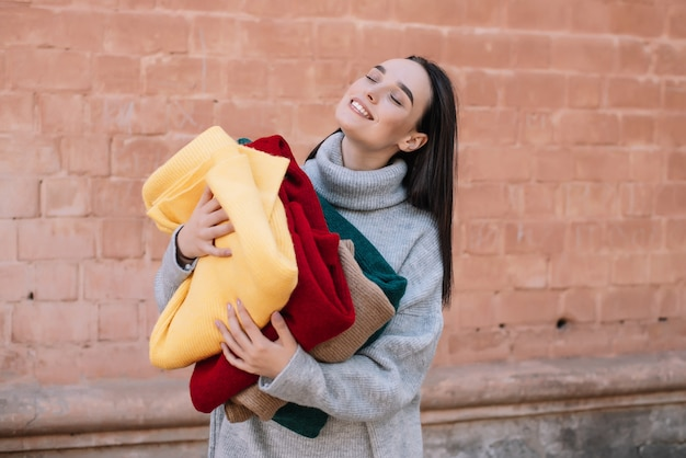 Positives mädchen möchte stilvolle kleidung kaufen, die strickjacken umarmen und einkaufszeit genießen. nahaufnahme porträt.