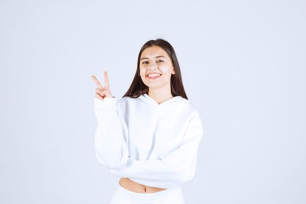 Positives modell des jungen mädchens, das victory-zeichen zeigt.