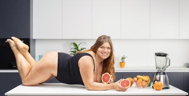 Positives molliges mädchen des sexy körpers, das auf dem küchentisch liegt und schwarzen badeanzug trägt, der eine frische grapefruit in den händen hält.