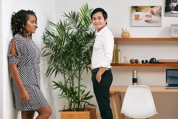 Positives multiethnisches geschäftsteam, das im modernen büro mit großem werk steht