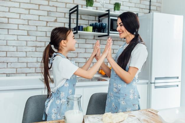 Positives nettes fröhliches mädchen, das einen teig hält, während es lernt, wie man kocht