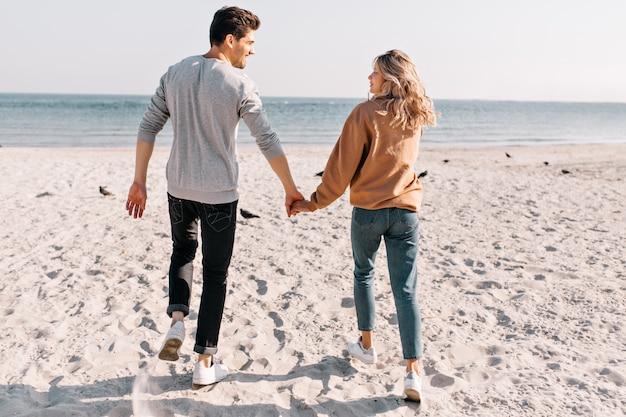 Positives paar, das mit lächeln zur see läuft. außenporträt des hübschen mädchens, das hände mit freund während der ruhe am strand hält.