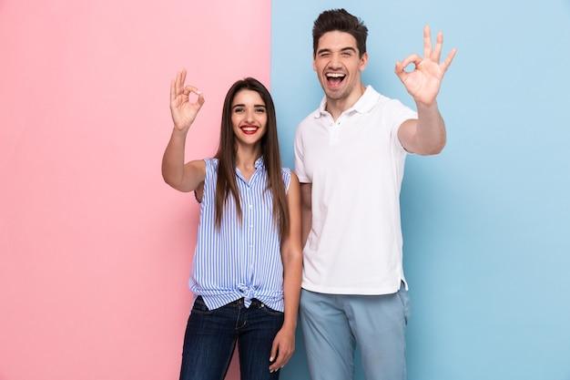 Positives paar in lässigen t-shirts lächelnd und gestikulierendes ok-zeichen, lokalisiert über bunte wand