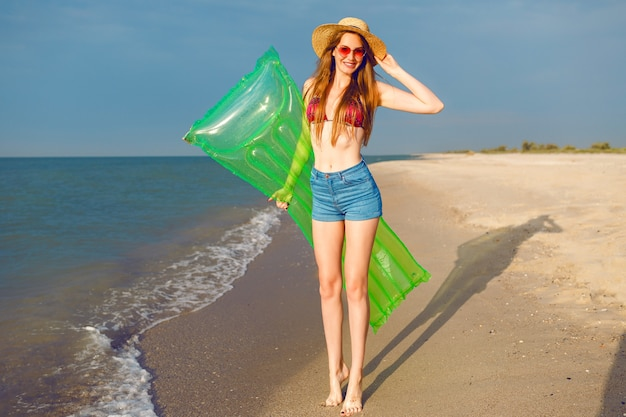 Positives porträt des hellen sommers des lebensstils der jungen hübschen hipster-frau, die spaß am strand hat