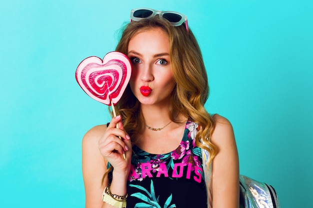 Positives porträt des studios der jungen sexy lustigen mode-verrückten frau, die auf blauem wandhintergrund im sommerart-outfit mit rosa lutscher aufwirft, der druckoberteil, neonrucksack und niedliche brille trägt.