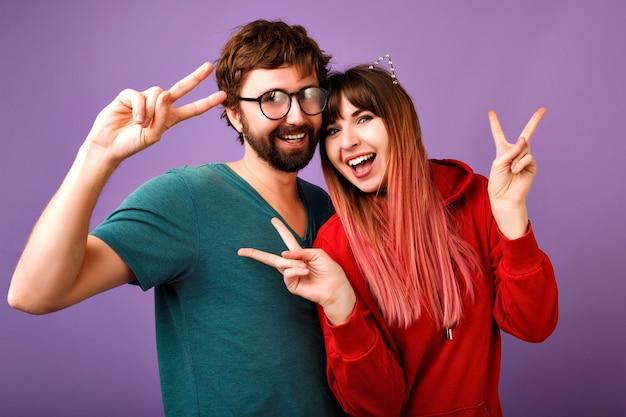 Positives porträt des verrückten jungen hipster-paares, das spaß zusammen hat, friedensgeste zeigt, die lacht und schreit, stilvolles lässiges kapuzenpulli und t-shirt, familien- und freundbild trägt