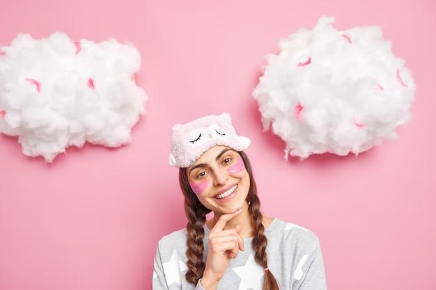 Positives sanftes kaukasisches weibliches modell hat zwei zöpfe, lächelt breit, neigt den kopf, trägt eine augenbinde und einen pyjama