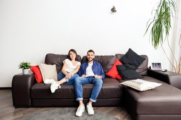 Positives schönes junges paar in jeans, die auf weichem sofa mit kissen sitzen und lächeln