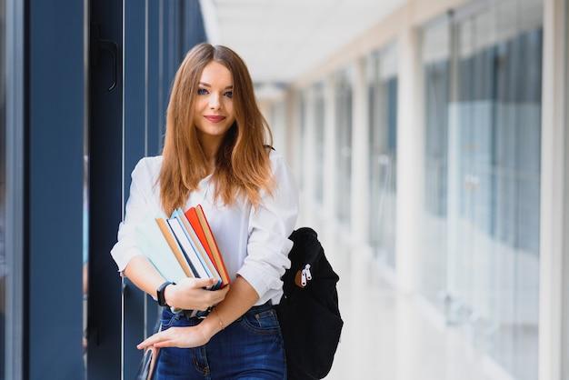 Positives schönes mädchen, das in die kamera lächelt und auf korridor mit notizen als rucksack steht und zur lektion geht