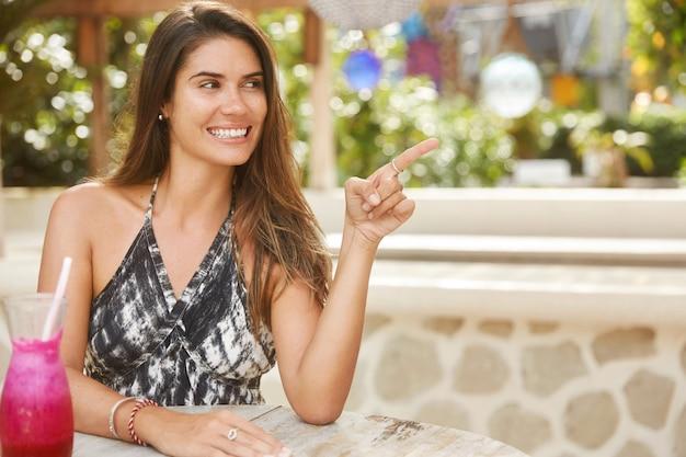 Positives schönes weibliches model ruht im restaurant, trinkt frischen sommercocktail, zeigt mit dem zeigefinger zur seite, hat glücklichen ausdruck, genießt gute ruhe. menschen-, erholungs- und freizeitkonzept.