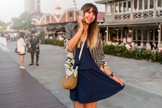 Positives sommerporträt der fröhlichen frau im stilvollen outfit, das per handy spricht und am flussufer in bangkok lächelt