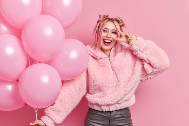 Positives, sorgloses, stilvolles tausendjähriges mädchen, das in einem warmen mantel gekleidet ist, lässt das friedenszeichen über dem auge lächeln glücklich hat partystimmung genießt den urlaub und hält einen haufen aufgeblasener luftballons