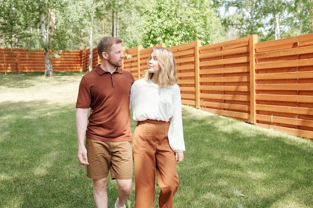 Positives verträumtes junges paar, das gegen neues haus mit glaswänden steht und umarmt, während es an zukunft denkt