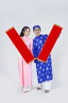 Positives vietnamesisches junges paar im traditionellen brauch für das neue mondjahr, bekannt als tet holiday