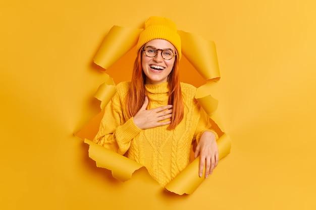Positives weibliches ingwermodell drückt aufrichtige gefühle aus, hält hand auf brust, fühlt dankbarkeit lächelt breit trägt gelbe kleidung bricht durch papier zerrissenes loch.
