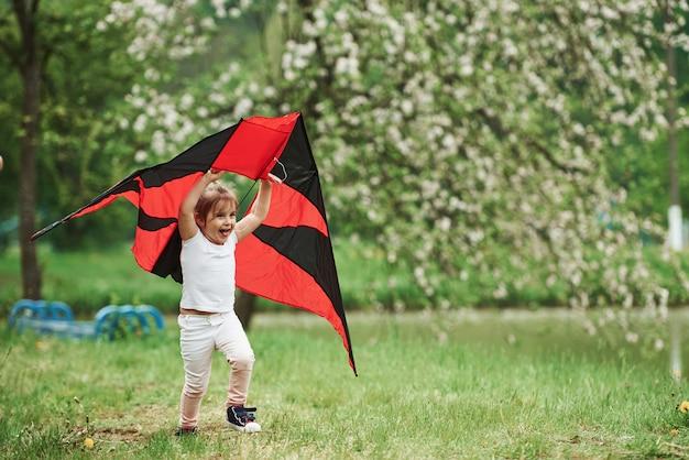 Positives weibliches kind, das mit rotem und schwarzem drachen in den händen draußen läuft