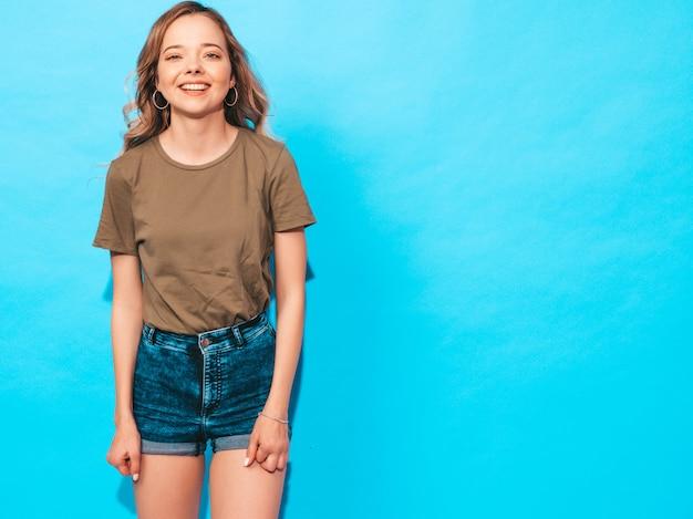 Positives weibliches lächeln. lustiges modell, das nahe blauer wand im studio aufwirft