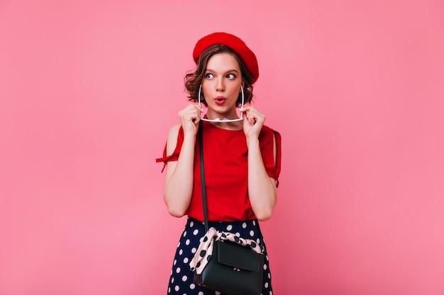 Positives weißes mädchen im niedlichen roten barett, das interesse ausdrückt. innenfoto des französischen weiblichen debonair-modells mit kurzem haarschnitt.