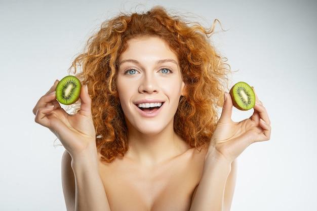 Positivität ausdrücken. erfreute junge frau, die ihr lächeln zeigt, während sie nach dem schießen obst isst