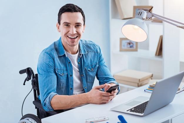 Positivität ausdrücken. junger ungültiger mann, der glück fühlt und zur arbeit geht