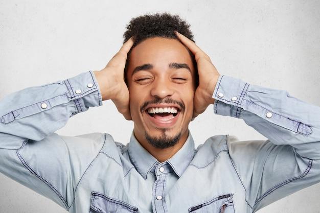Positivitäts- und glückskonzept. ich bin froh, dass ein emotionaler mann einen schnurrbart hat und der bart vor vergnügen die augen schließt. er freut sich, etwas über den sieg der konkurrenz zu erfahren, isoliert über dem weißen hintergrund