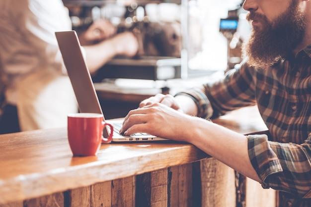 Post aus dem café schreiben. nahaufnahme eines jungen bärtigen mannes, der seinen laptop benutzt, während er an der bartheke im café mit barista im hintergrund sitzt