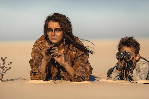 Postapokalyptische frau und junge mit fernglas im freien. wüste und totes ödland auf der