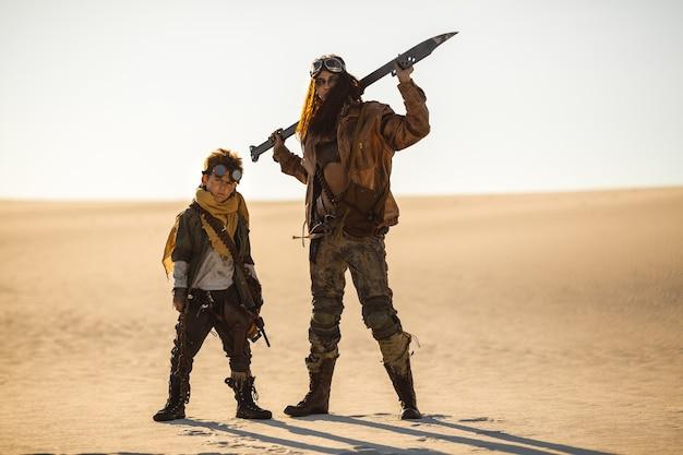 Postapokalyptische frau und junge mit waffen im freien. wüste und totes ödland im hintergrund