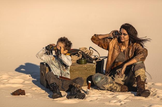 Postapokalyptische heldenfrau und -junge mit fernglas im freien. wüste und totes ödland auf der