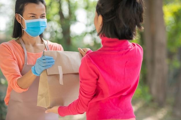 Postbote, zusteller mit maske tragen eine kleine schachtel, die an den kunden vor der tür zu hause geliefert wird. frau, die maske trägt, verhindert covid 19, den ausbruch einer coronavirus-infektion. einkaufskonzept für die lieferung nach hause.