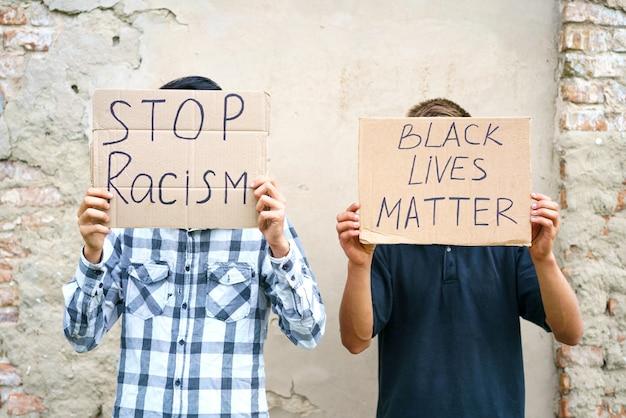 Poster, auf dem steht, dass schwarzes leben wichtig ist und rassismus in den händen eines jungen mannes, der kaukasischen mann inszeniert, stoppt...