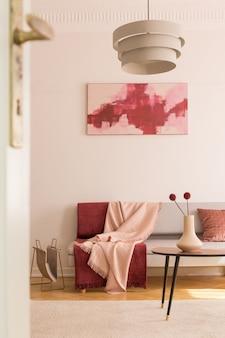 Poster über dem sofa mit decken im loft-interieur mit lampe über dem tisch mit blumen. echtes foto
